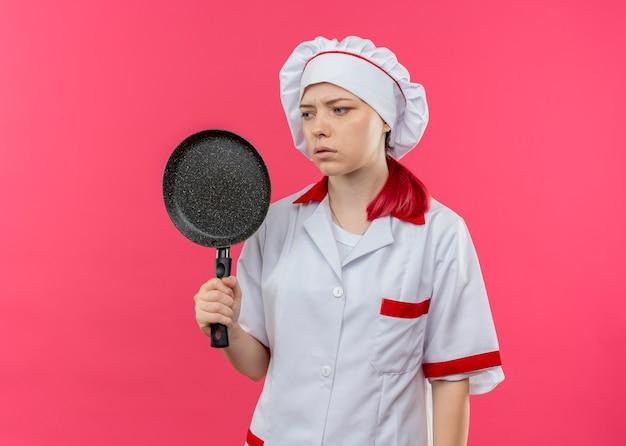 シェフの制服を着た若いイライラする金髪の女性シェフは、フライパンを保持し、ピンクの壁で隔離された側に見えます