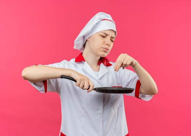 シェフの制服を着た若いイライラする金髪の女性シェフは、フライパンを保持し、ピンクの壁に隔離された目を閉じて塩のふりをします