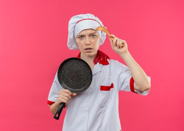 シェフの制服を着た若いイライラする金髪の女性シェフは、ピンクの壁で隔離のフライパンとスプーンを保持します