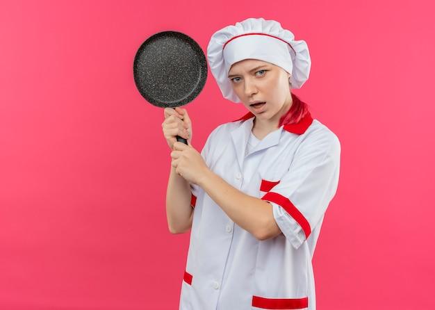 シェフの制服を着た若いイライラする金髪の女性シェフは、ピンクの壁に分離された両手でフライパンを保持します。