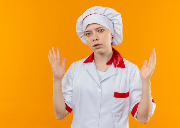 シェフの制服を着た若いイライラする金髪の女性シェフは、オレンジ色の壁に隔離された手を持ち上げます