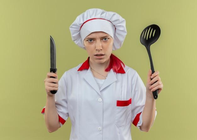 シェフの制服を着た若いイライラする金髪の女性シェフは、緑の壁に分離されたナイフとヘラを保持します