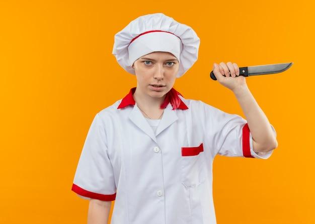 シェフの制服を着た若いイライラする金髪の女性シェフは、オレンジ色の壁に分離されたナイフを保持します
