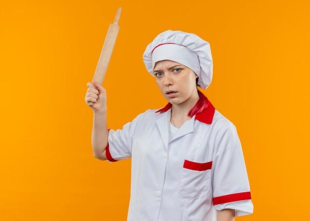 シェフの制服を着た若いイライラする金髪の女性シェフはめん棒を保持し、オレンジ色の壁に孤立して見える
