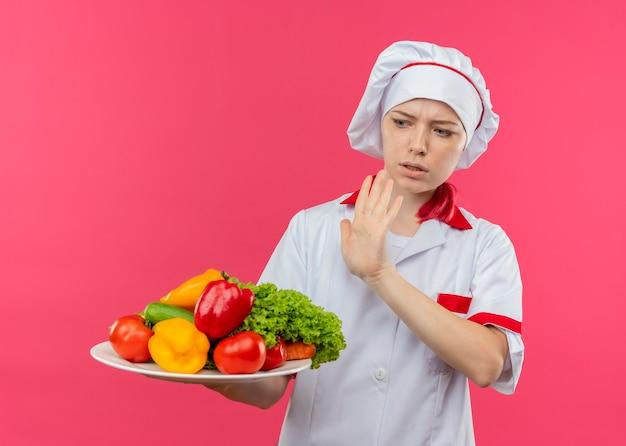 シェフの制服を着た若いイライラする金髪の女性シェフは、皿に野菜を保持し、ピンクの壁に隔離された手で押すふりをします