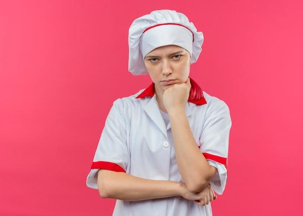 シェフの制服を着た若いイライラする金髪の女性シェフは、ピンクの壁に分離されたあごに拳を置きます