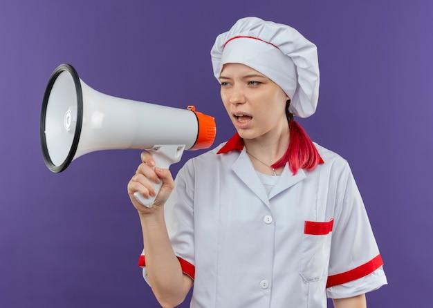 紫色の壁に隔離されたスピーカーを通してシェフの制服を着た若いイライラする金髪の女性シェフが叫ぶ