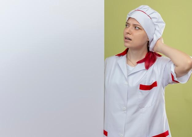 シェフの制服を着た若いイライラする金髪の女性シェフが後ろに立って、緑の壁に隔離された白い壁を見てください