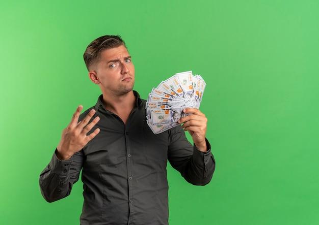 若いイライラする金髪のハンサムな男はお金を保持し、コピースペースで緑の背景に分離された4つのジェスチャー