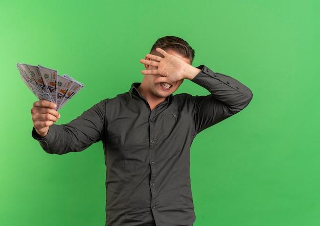 Молодой раздраженный блондин красавец держит деньги и прячет лицо рукой, изолированной на зеленом пространстве с копией пространства