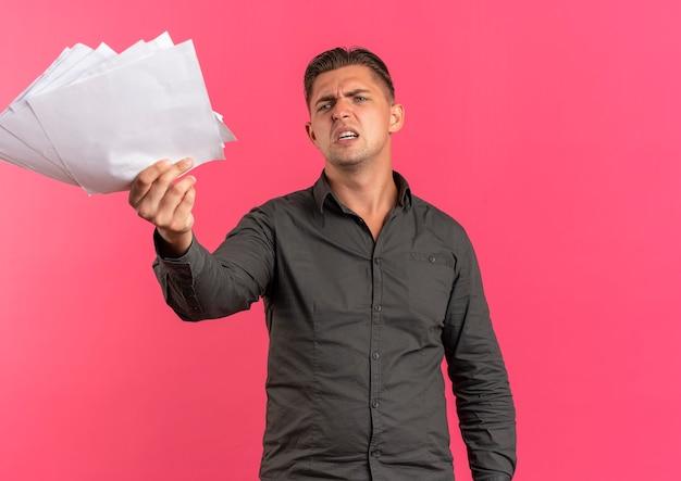 Il giovane uomo bello biondo infastidito tiene i fogli di carta che guardano in avanti isolato sullo spazio rosa con lo spazio della copia