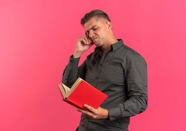 젊은 화가 금발의 잘 생긴 남자가 머리에 손을 넣고 복사 공간이 분홍색 배경에 고립 된 책을 본다