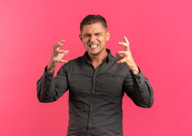 若いイライラする金髪のハンサムな男は、コピースペースでピンクのスペースに分離された指を絞る