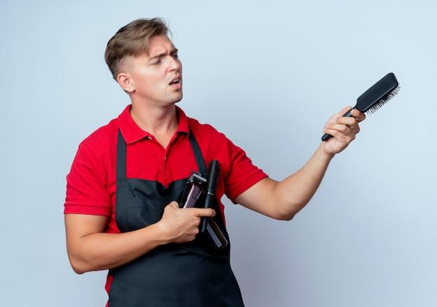 Молодой раздраженный блондин мужчина-парикмахер в униформе держит инструменты парикмахера, указывая в сторону с гребнем, изолированным на белом пространстве с копией пространства