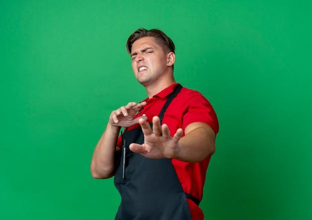 제복을 입은 젊은 화가 금발 남성 이발사는 복사 공간이있는 녹색 공간에 고립 된 손을 뻗어 밀어내는 척합니다.