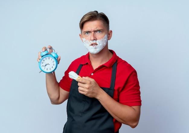 Молодой раздраженный светловолосый парикмахер в униформе, измазанный пеной для бритья, держит будильник и кисточку для бритья, изолированную на белом пространстве с копией пространства