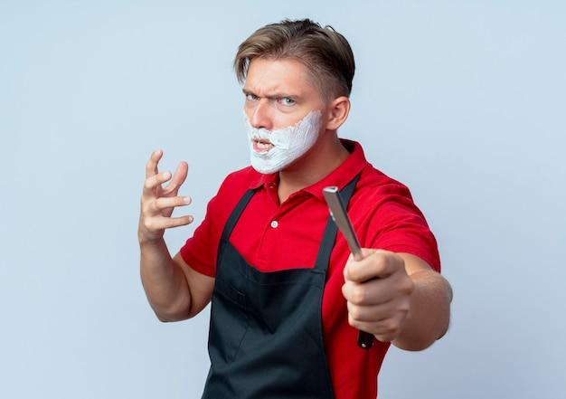Молодой раздраженный светловолосый парикмахер в униформе измазал лицо пеной для бритья, держа опасную бритву, изолированную на белом пространстве с копией пространства