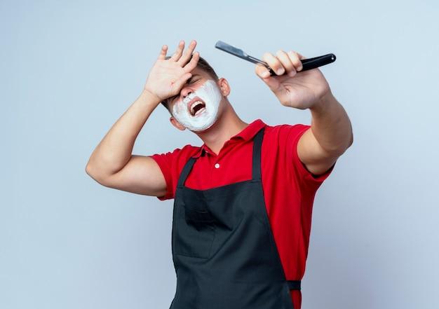 Молодой раздраженный светловолосый парикмахер в униформе измазал лицо пеной для бритья, держа опасную бритву, положив руку на лоб, изолированный на белом пространстве с копией пространства
