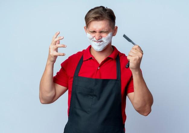 Молодой раздраженный светловолосый парикмахер в униформе, измазанный пеной для бритья, держит опасную бритву с закрытыми глазами, изолированными на белом пространстве с копией пространства