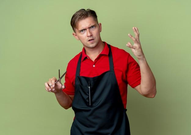 制服を着た若いイライラする金髪の男性理髪師は、上げられた手の指を絞って、コピースペースでオリーブグリーンのスペースに分離されたはさみを保持します