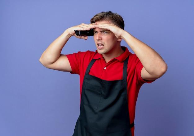 Il giovane barbiere maschio biondo infastidito in uniforme mantiene il palmo sulla fronte che tiene il tagliatore di capelli cercando di vedere qualcosa di distante isolato sullo spazio viola con lo spazio della copia