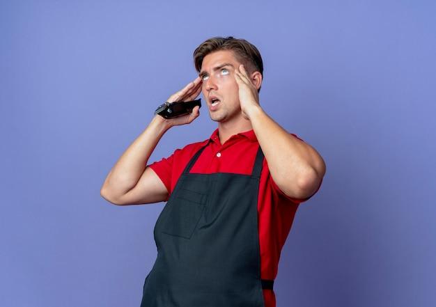 Il giovane barbiere maschio biondo infastidito in uniforme mette le mani sulle tempie che tengono il tagliatore di capelli isolato sullo spazio viola con lo spazio della copia