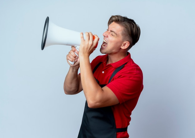 Young annoyed blonde male barber in uniform shouts into loud speaker isolated on white background with copy space