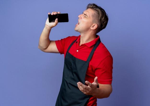 Il giovane barbiere maschio biondo infastidito in uniforme sta lateralmente tenendo il telefono e fingendo di cantare isolato sullo spazio viola con lo spazio della copia
