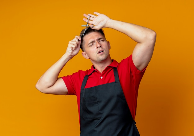 Barbiere maschio biondo infastidito giovane in uniforme che prova a tagliare i suoi capelli con il pettine e le forbici isolati sullo spazio arancio con lo spazio della copia