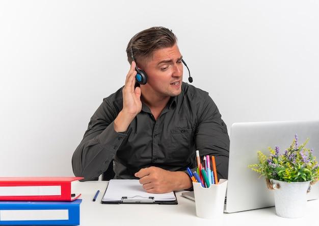 Giovane uomo di lavoratore di ufficio bionda infastidito sulle cuffie si siede alla scrivania con strumenti per ufficio utilizzando il computer portatile tiene le cuffie cercando di ascoltare isolato su sfondo bianco con spazio di copia