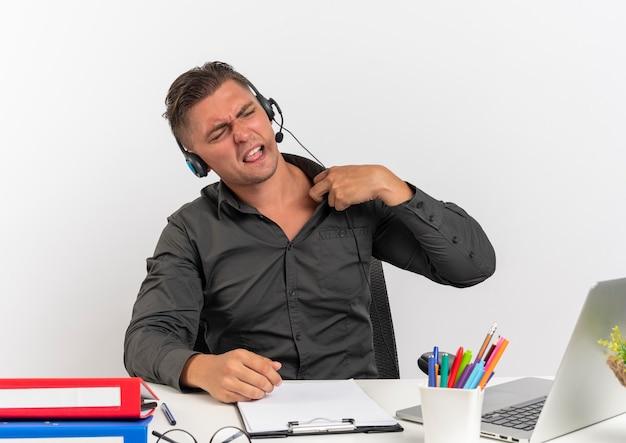 헤드폰에 젊은 화가 금발 회사원 남자는 노트북을 사용하는 사무실 도구와 책상에 앉아 복사 공간 흰색 배경에 고립 된 칼라를 보유