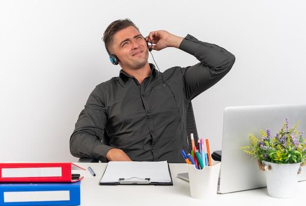 ヘッドフォンで若いイライラする金髪のサラリーマンの男は、ラップトップを使用してオフィスツールで机に座ってコピースペースで白い背景に分離されたヘッドフォンを保持します