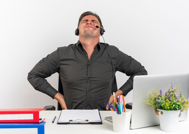 Молодой раздраженный белокурый человек офисного работника в наушниках сидит за столом с офисными инструментами, используя ноутбук, держит спину, глядя вверх, изолированные на белом фоне с копией пространства