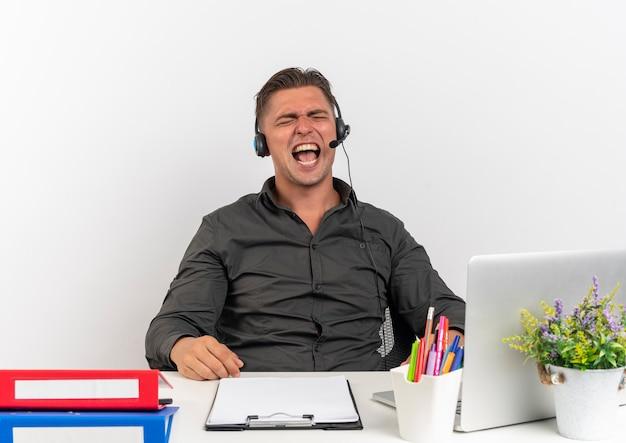 헤드폰에 젊은 화가 금발 회사원 남자 복사 공간이 흰색 배경에 고립 된 닫힌 눈으로 노트북 비명을 사용하여 사무실 도구와 책상에 앉아