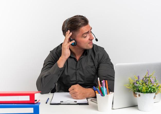 ヘッドフォンで若いイライラする金髪のサラリーマンの男は、コピースペースで白い背景で隔離を聞くことを試みているラップトップを使用してオフィスツールで机に座っています