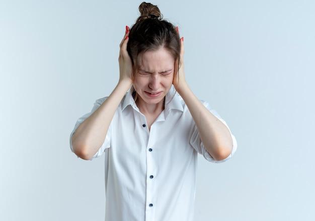 La giovane ragazza russa bionda infastidita closses le orecchie con le mani isolate su uno spazio bianco con lo spazio della copia