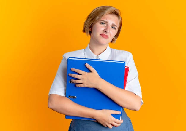 Young annoyed blonde russian girl holds file folders isolated on orange background with copy space