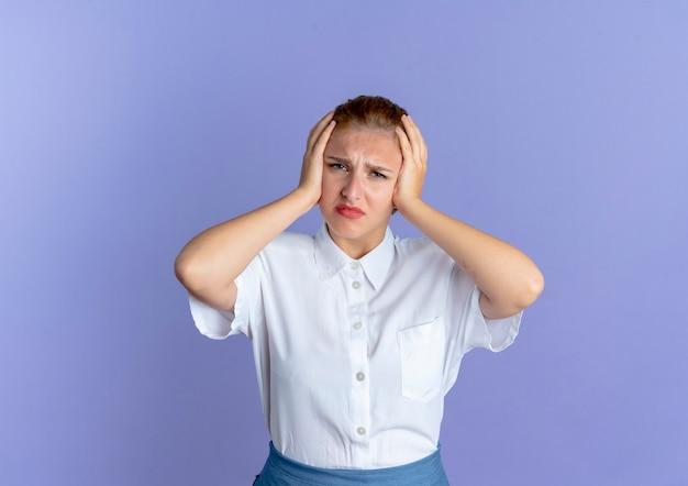 Молодая раздраженная русская блондинка держит голову изолированной на фиолетовом фоне с копией пространства