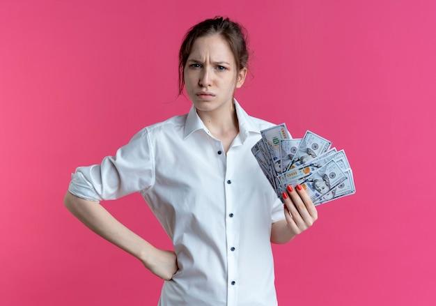 若いイライラする金髪のロシアの女の子は、コピースペースでピンクのカメラを見てお金を保持します