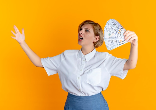 Young annoyed blonde russian girl holds money looking at side with raised hand isolated on orange background with copy space