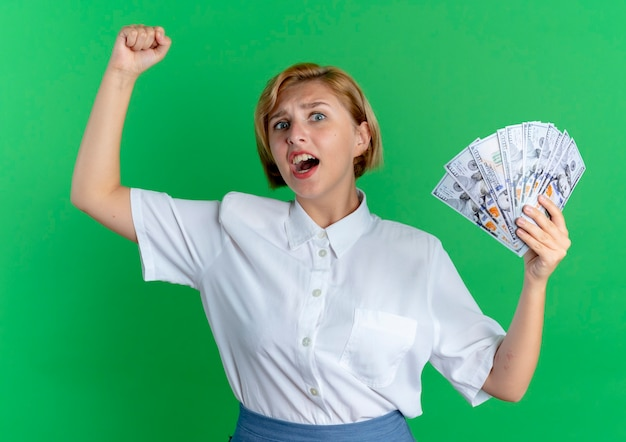 Young annoyed blonde russian girl holds money with raised fist isolated on green background with copy space