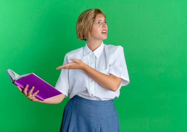 La giovane ragazza russa bionda infastidita tiene e indica il libro che esamina il lato isolato su fondo verde con lo spazio della copia