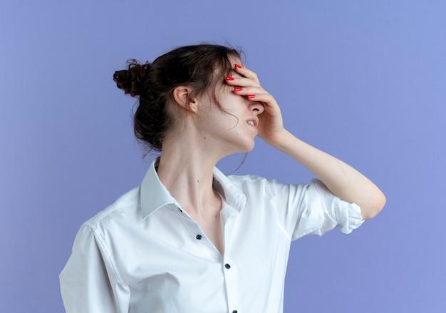 Молодая раздраженная русская блондинка кладет руку на лицо на фиолетовый с копией пространства