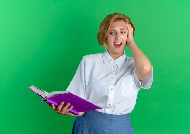 Молодая раздраженная русская блондинка кладет руку на голову, глядя на книгу, изолированную на зеленом фоне с копией пространства