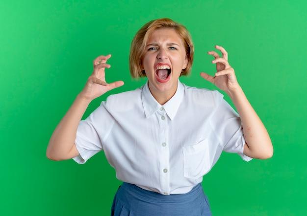 若いイライラする金髪のロシアの女の子は、コピースペースで緑の背景に分離された指を絞って誰かに怒鳴ります