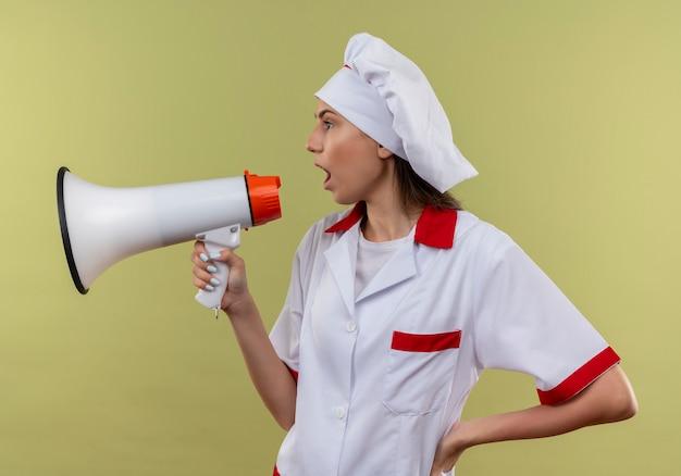 La giovane ragazza caucasica infastidita del cuoco in uniforme del cuoco unico sta lateralmente e grida tramite l'altoparlante su verde con lo spazio della copia