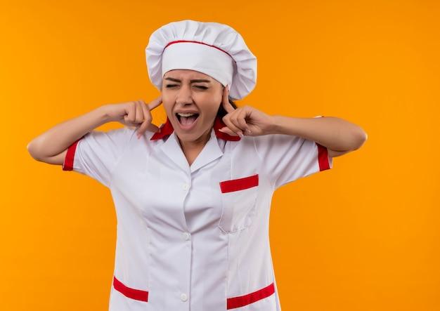 シェフの制服を着た若いイライラする白人料理人の女の子は、コピースペースでオレンジ色の背景に分離された指で耳を閉じます