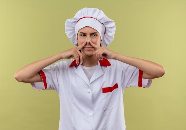 シェフの制服を着た若いイライラする白人料理人の女の子は、鼻を閉じて、コピースペースで緑の側を見ます