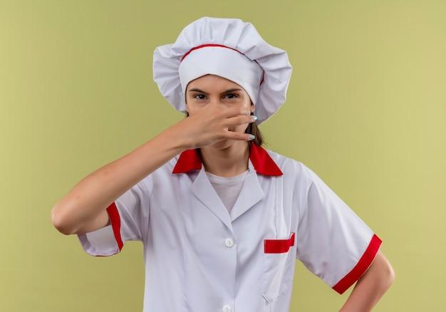 シェフの制服を着た若いイライラする白人料理人の女の子は、コピースペースで緑に手で鼻を閉じます