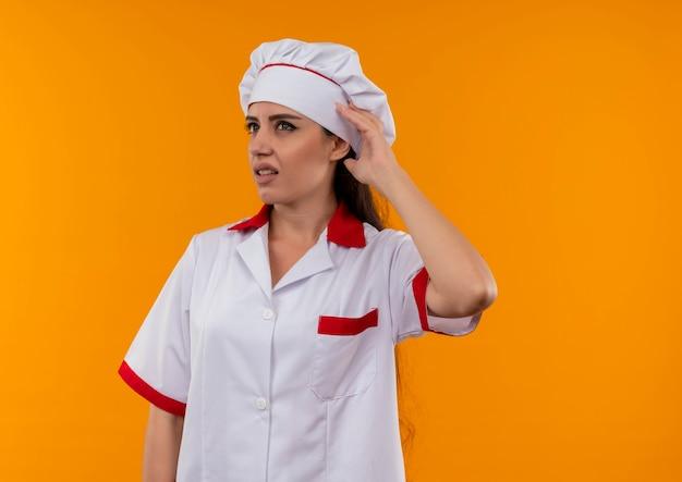 シェフの制服のジェスチャーで若いイライラする白人料理人の女の子は、コピースペースでオレンジ色の背景に分離されたサインを聞くことができません